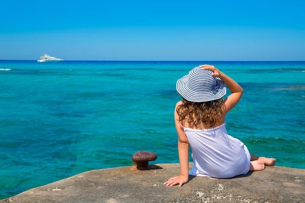 Mädchen, das strand in formentera-türkis mittelmeer betrachtet