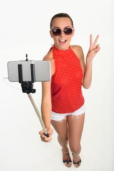 Mädchen, das stückzeichen unter selfie zeigt.