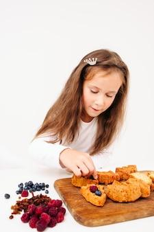 Mädchen, das süße kuchen mit beeren vorbereitet