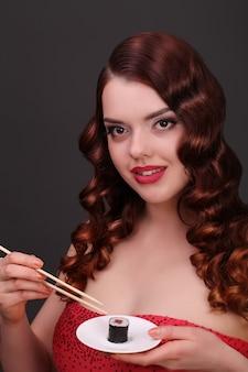 Mädchen, das sushi mit essstäbchen isst