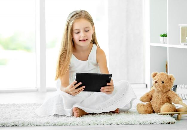 Mädchen, das tablet-computer spielt
