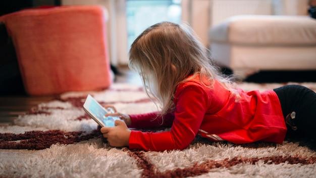 Mädchen, das tablette auf teppich verwendet