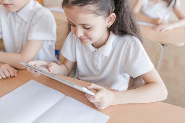 Mädchen, das tablette während der lektion verwendet