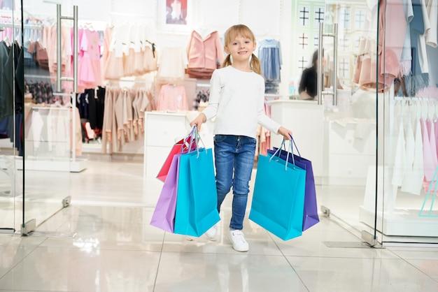 Mädchen, das taschen hält und kamera beim einkaufen betrachtet