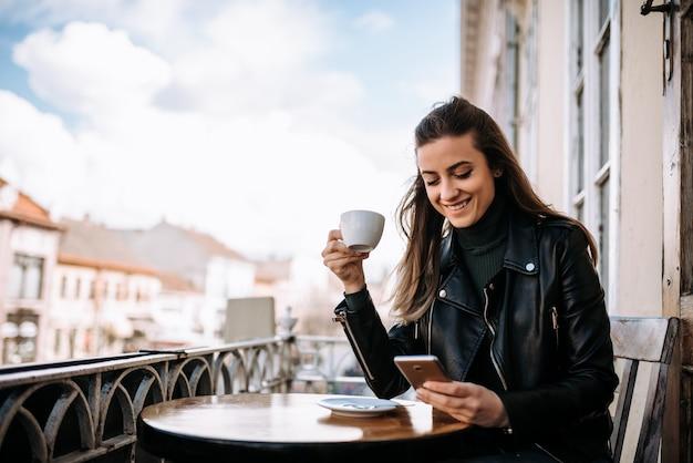 Mädchen, das tasse kaffee bei der anwendung des telefons auf dem balkon genießt.