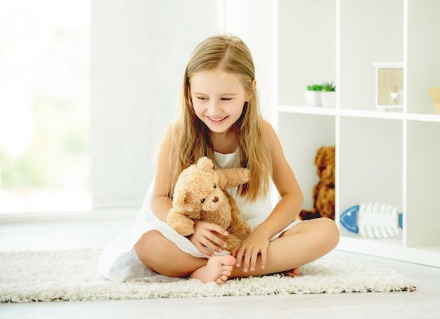 Mädchen, das teddybären umarmt