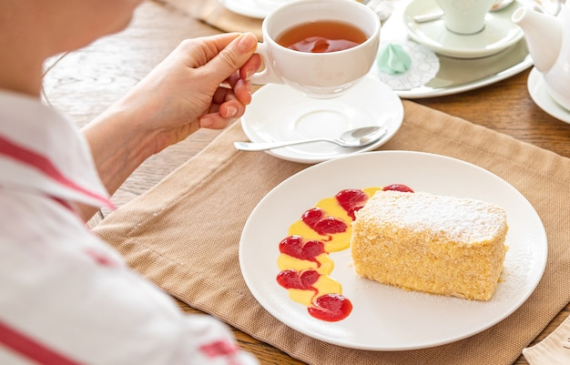 Mädchen, das tee mit kuchen napoleon trinkt. ein stück napoleon-kuchen auf einem weißen teller auf einem servierten tisch. im hintergrund gibt es einen wasserkocher, tee, saft.