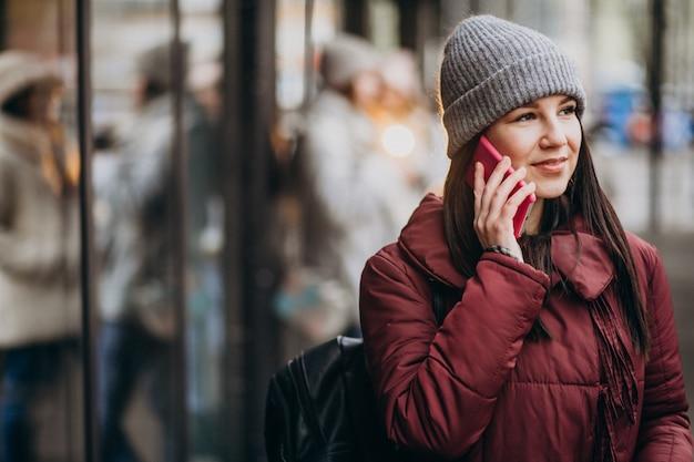Mädchen, das telefon außerhalb der straße verwendet und freunde trifft