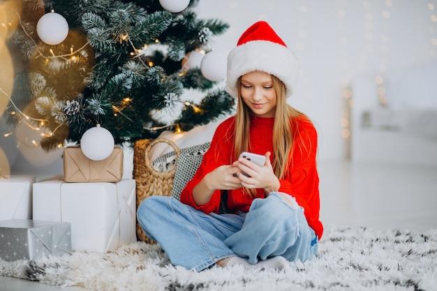 Mädchen, das telefon durch weihnachtsbaum an weihnachten benutzt