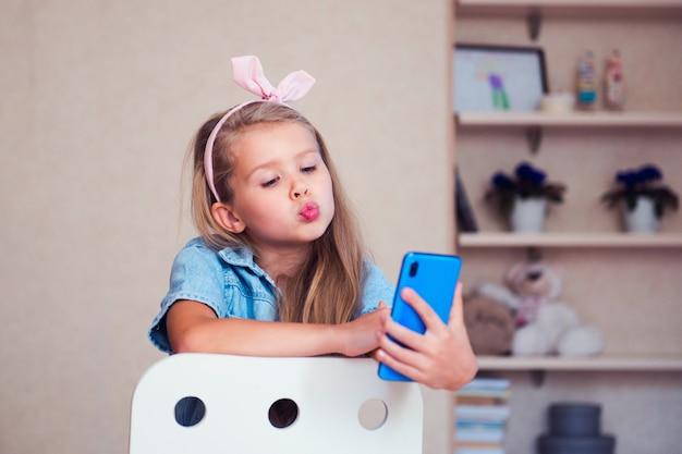 Mädchen, das telefonbildschirm beobachtet oder mit freunden chattet
