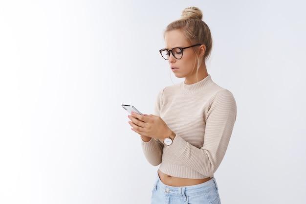 Mädchen, das traurige nachrichten über smartphone empfängt. porträt einer verärgerten, gut aussehenden blonden frau mit brille, die die stirn runzelt, traurig aussehend handy-bildschirm unzufrieden und unglücklich posiert auf weißem hintergrund
