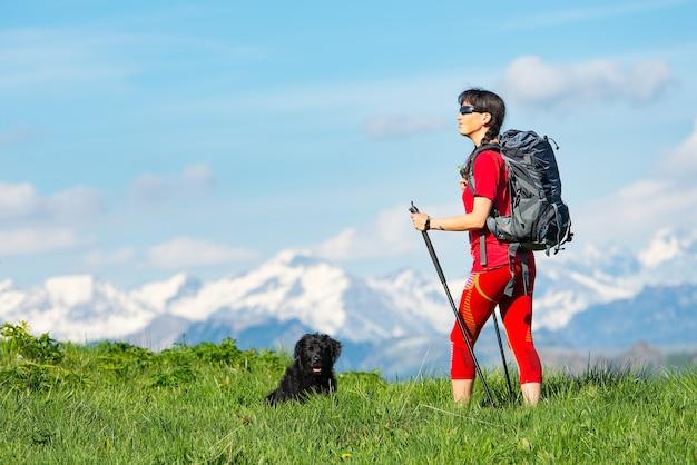 Mädchen, das trekking in den bergen mit seinem hirtenhund auf dem gras mit montahe des schneehintergrundes praktiziert