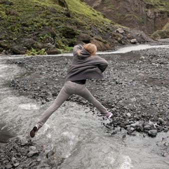 Mädchen, das über schnell fließenden strom mit felsigem riverbank springt