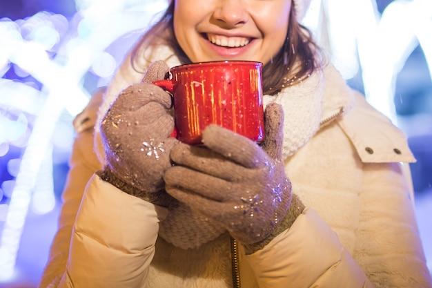 Mädchen, das über winterweihnachtsstadthintergrund schneeschneeverwehungen steht, steht warme jacke hut hält
