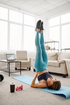 Mädchen, das übung auf der presse, online-fit-training am laptop macht. weibliche person in sportbekleidung, internet-sporttraining, rauminnenraum