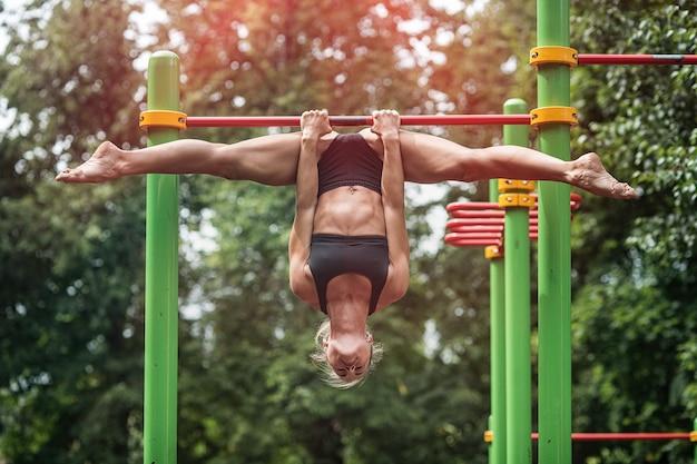 Mädchen, das übungen auf der horizontalen stange tut. die frau ist mit dem training beschäftigt