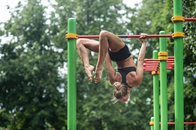 Mädchen, das übungen auf der horizontalen stange tut. die frau nimmt am training teil