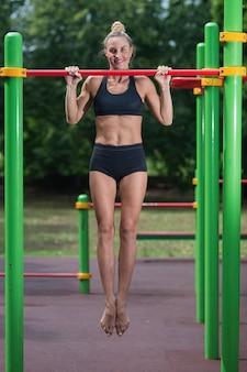 Mädchen, das übungen auf der horizontalen stange tut die frau nimmt an training teil