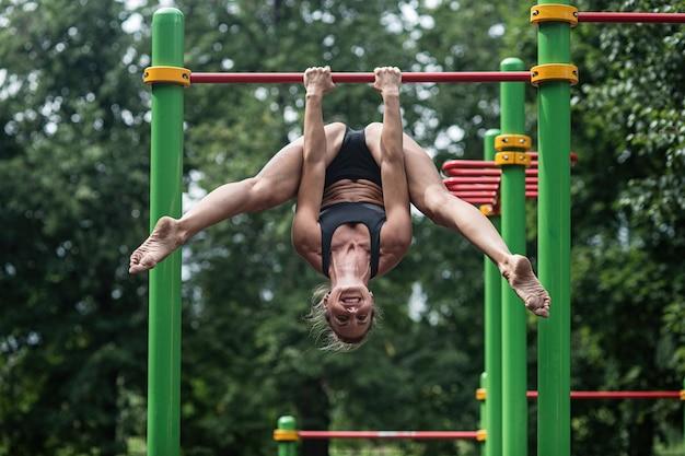 Mädchen, das übungen auf der horizontalen stange tut.