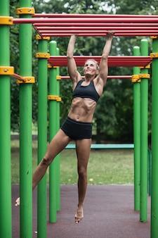 Mädchen, das übungen auf der horizontalen stange tut