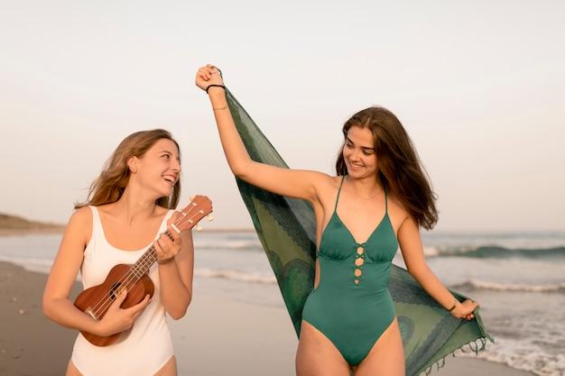 Mädchen, das ukulele mit ihrem freund hält schal am strand spielt