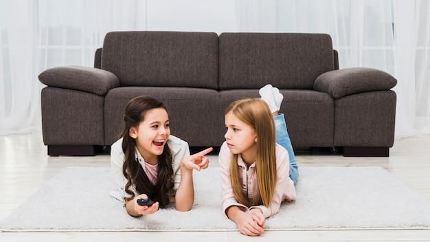 Mädchen, das unfug ihres freunds zu hause liegt auf teppich macht