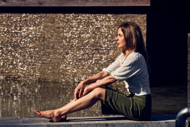 Mädchen, das unter der sonne nahe dem wasser am schwülen heißen tag sich entspannt