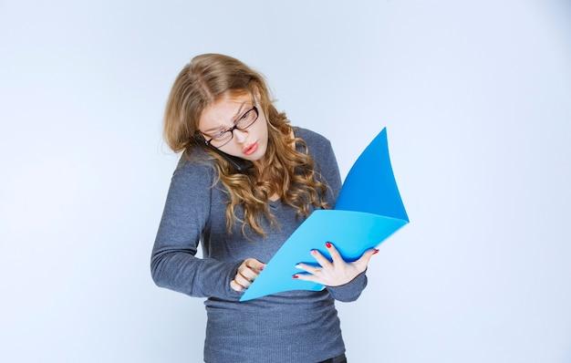 Mädchen, das unzufrieden mit dem telefon spricht und korrekturen an ihrem blauen ordner vornimmt.