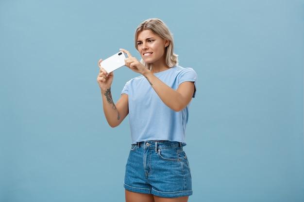 Mädchen, das versucht, foto mit smartphone zu machen