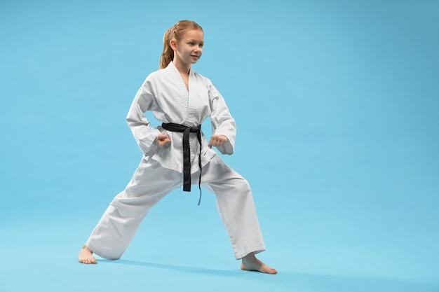Mädchen, das verteidigungsposition des karate durchführt.