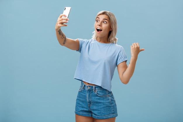 Mädchen, das video aufzeichnet, das anhänger fantastische szene zeigt, die rückwärts zeigt und rechts anzeigt
