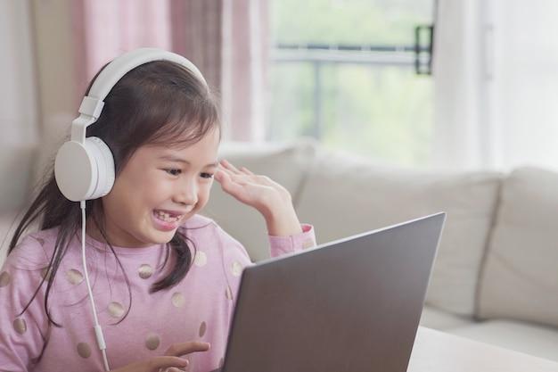 Mädchen, das videoanruf mit laptop zu hause macht