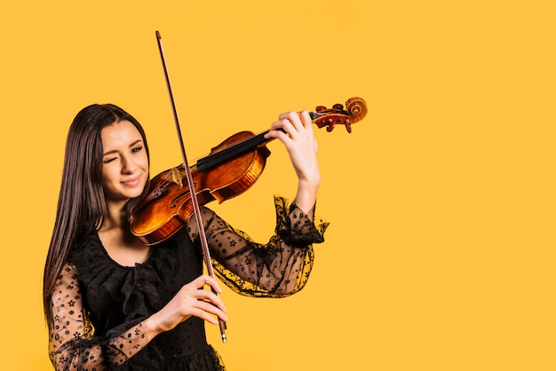 Mädchen, das violine spielend zwinkert