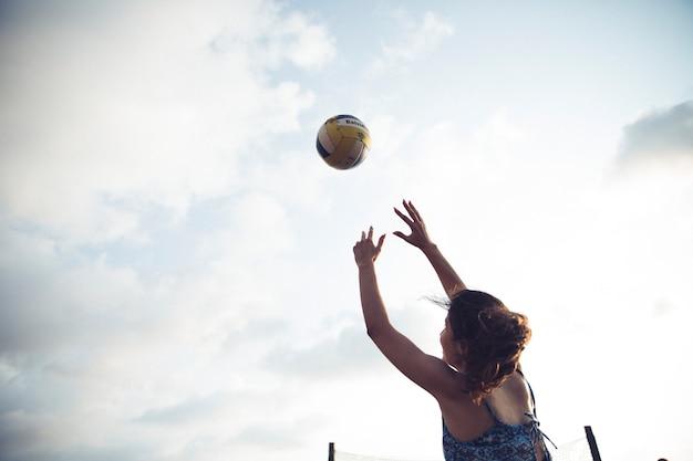 Mädchen, das volleyball am strand spielt