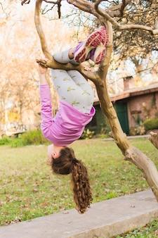 Mädchen, das vom baumzweig im park baumelt
