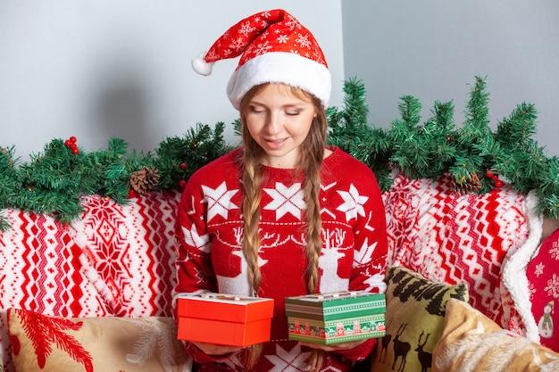 Mädchen, das von zwei weihnachtsgeschenkboxen in den feiertagsdekorationen des neuen jahres wählt