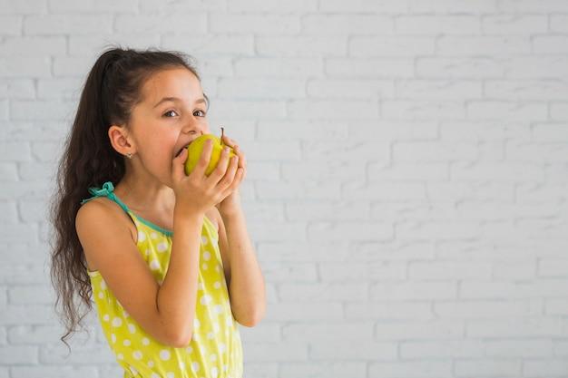 Mädchen, das vor der wand isst grünen apfel steht