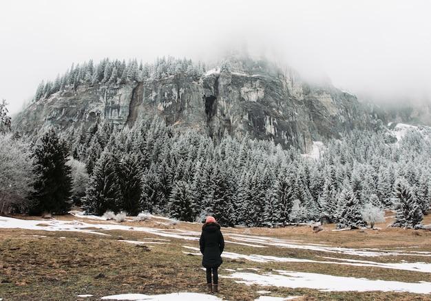 Mädchen, das vor felsen und einem wald steht, der im schnee unter einem bewölkten himmel bedeckt ist