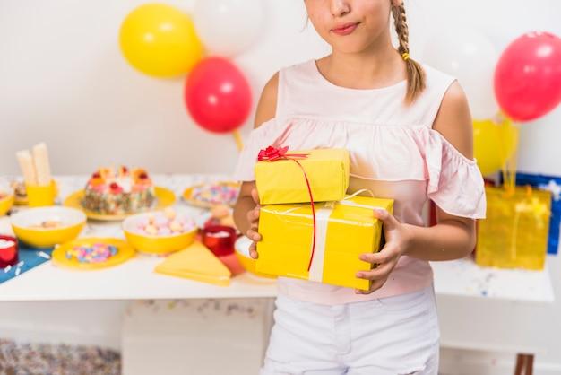 Mädchen, das vor tabelle mit geschenken in ihrer hand steht