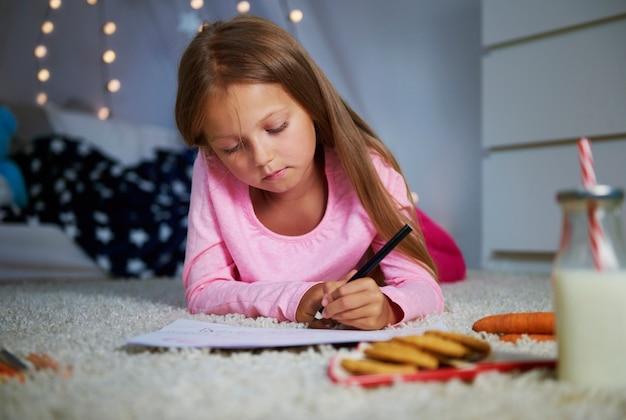 Mädchen, das vorne liegt und einen brief schreibt
