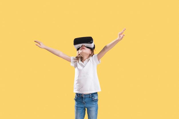 Mädchen, das vr-kopfhörerspiel auf buntem erfährt. überraschte gefühle auf ihrem gesicht. kind, das ein spielgerät für virtuelle realität verwendet.