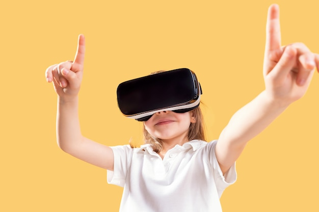 Mädchen, das vr-kopfhörerspiel erfährt. überraschte gefühle auf ihrem gesicht. kind, das ein spielgerät für virtuelle realität verwendet.
