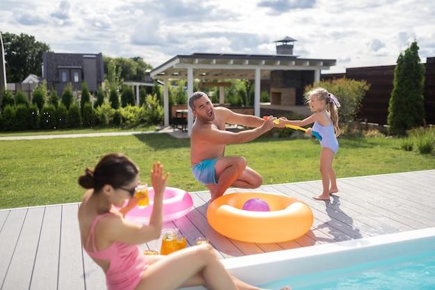 Mädchen, das wasser spritzt. lustiges mädchen, das einen schönen badeanzug trägt und wasser auf die eltern in der nähe des pools spritzt?