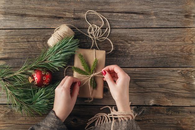 Mädchen, das weihnachtsgeschenk einwickelt. die hände der frau, die verzierte geschenkbox auf rustikalem holztisch halten. weihnachten oder neujahr diy verpackung. obenliegende, flache lage, ansicht von oben