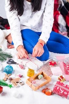 Mädchen, das weihnachtskarten und dekorationen für familie und weihnachtsbaum macht. feiern, geburtstagsfeier, geschenke,