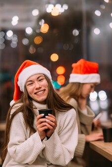 Mädchen, das weihnachtsmannhut sitzt im kaffeehaus sitzt und kaffee trinkt