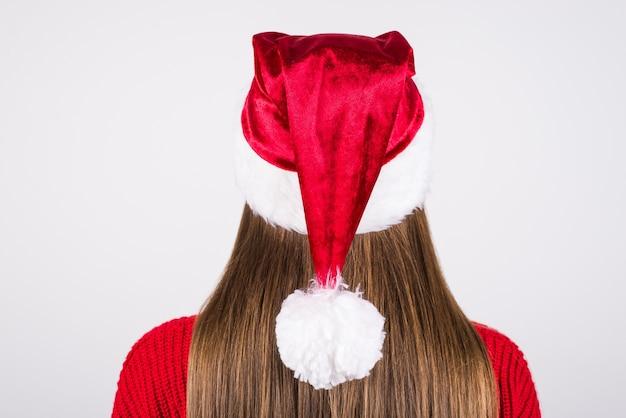 Mädchen, das weihnachtsmütze und roten pullover trägt