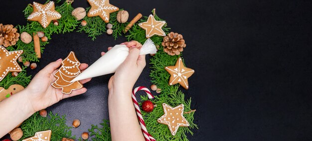 Mädchen, das weihnachtsplätzchen zu hause verziert.