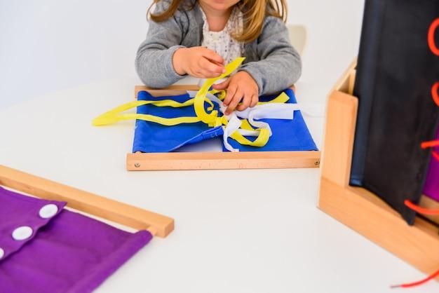 Mädchen, das wie man bindungen in einem holzrahmen übt, bindet.