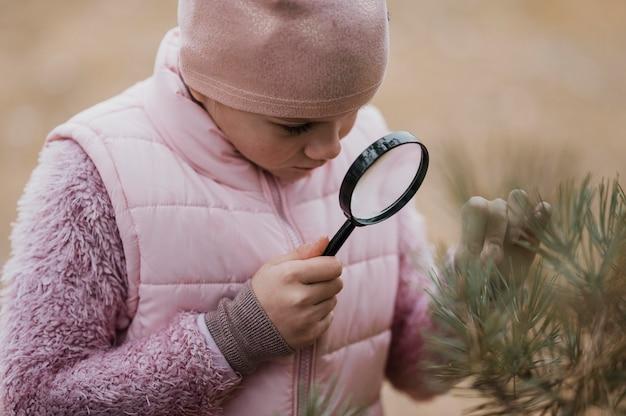 Mädchen, das wissenschaft in der natur mit einer lupe lernt
